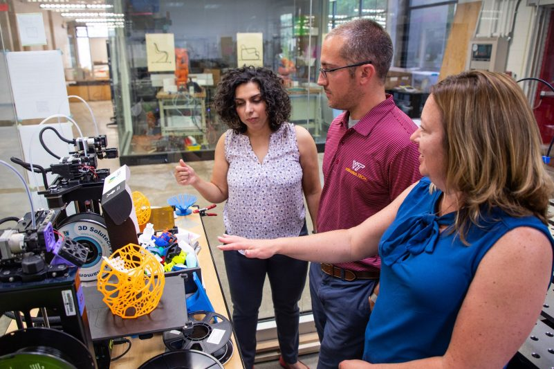 Faculty discuss possible fabrication methods in the 3D printing lab