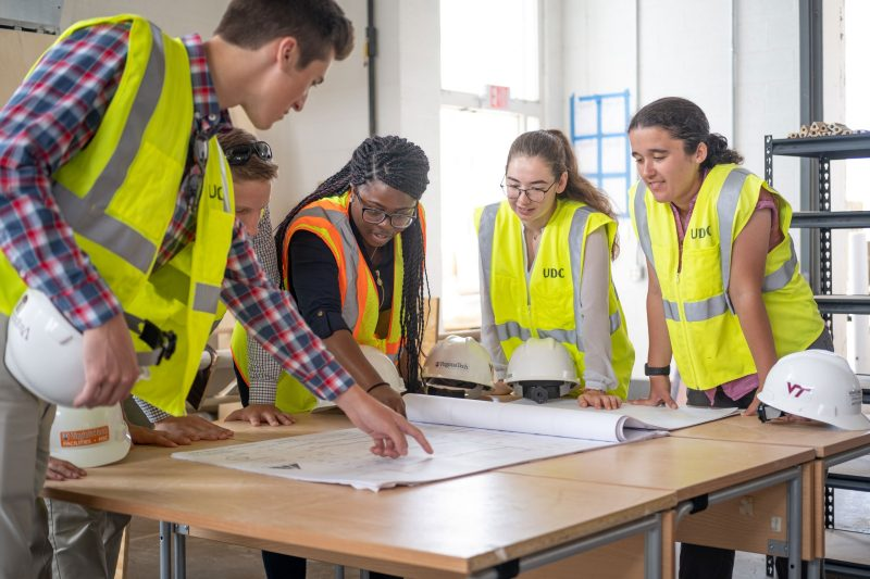 Students examine building plans at the Research + Demonstration Facility