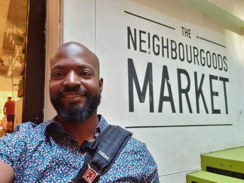Head shot of Ph.D. student Davon Woodard outside Neighborhoods Market in Johannesburg
