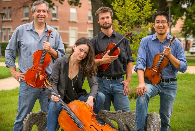 The Ceruti String Quartet poses for an outdoor photo with their instruments.