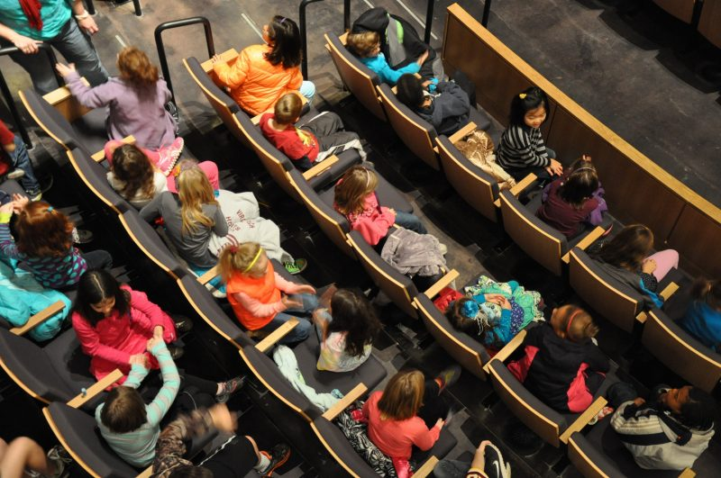 A group of students sit in their seats in the Moss Arts Center theatre.