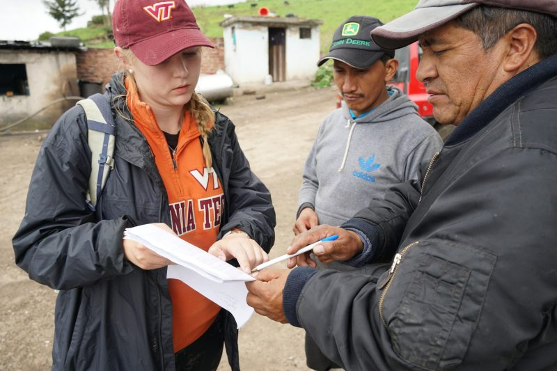Madi Dynes looks at a list of farms with Ecuadorian partners during survey fieldwork.