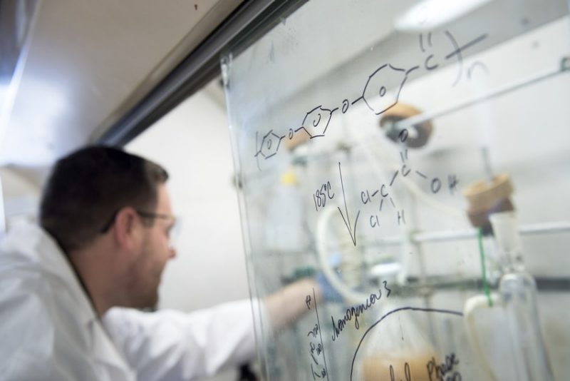 A science researcher works under the hood in the background. A science equation is written on a board in the foreground.