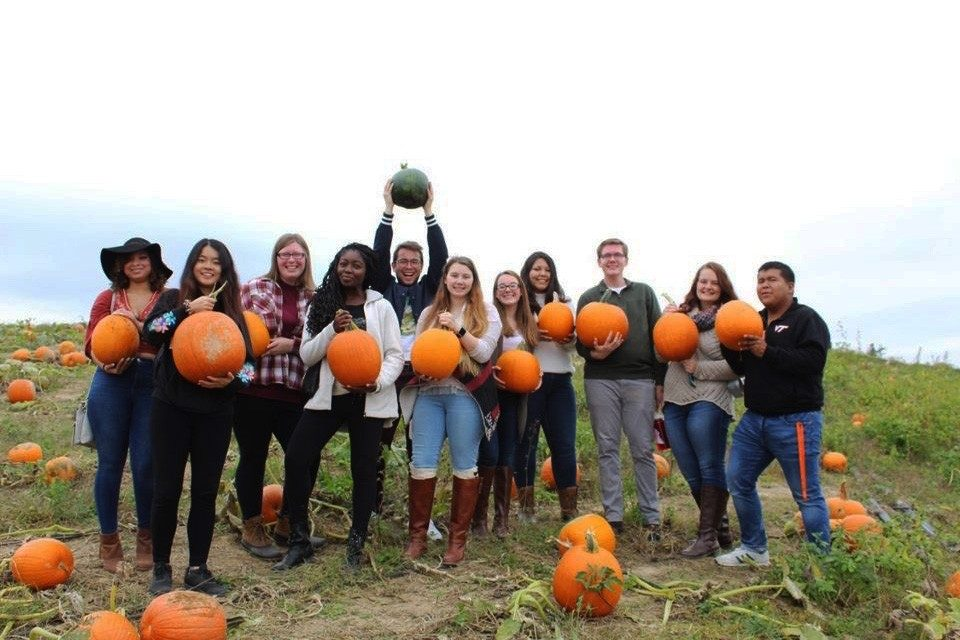 Mason Stoecker (center, holding up green pumpkin) poses with transfer students in a pumpkin patch.