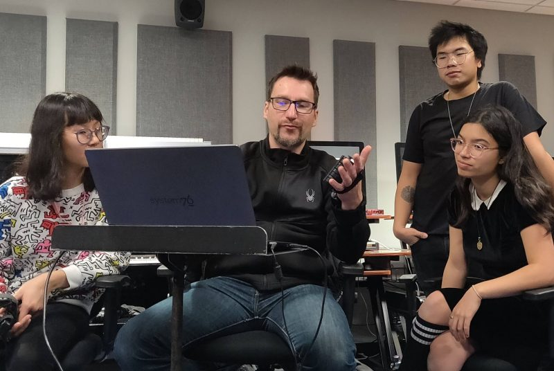 Professor Ico Bukvic is surrounded by three students in the music lab.