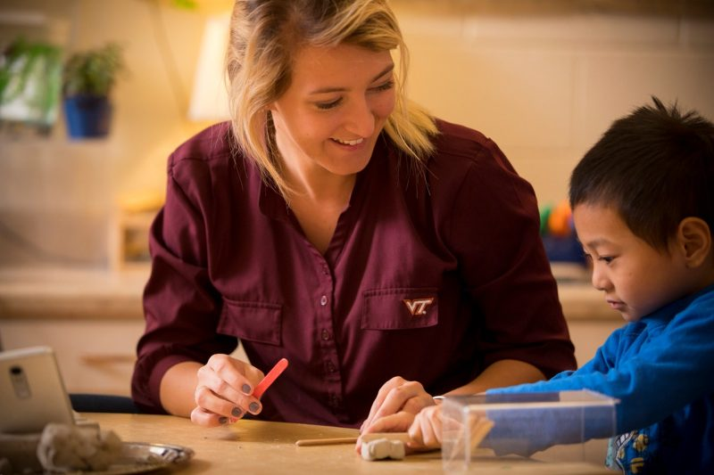 Emily Phillips does a craft activity with a young boy