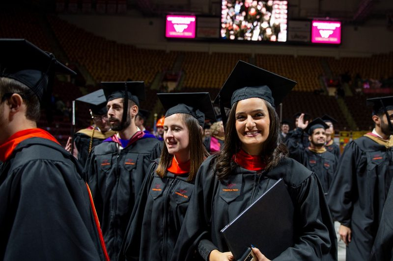 Newly conferred Virginia Tech graduates wearing black caps and gowns with orange embellishments leave Cassell Coliseum during 2018 fall commencement exercises.