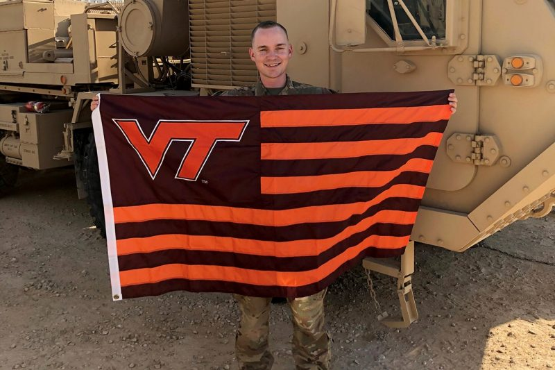 2nd Lt. William Breedlove  holds a Hokie flag while deployed to Iraq.