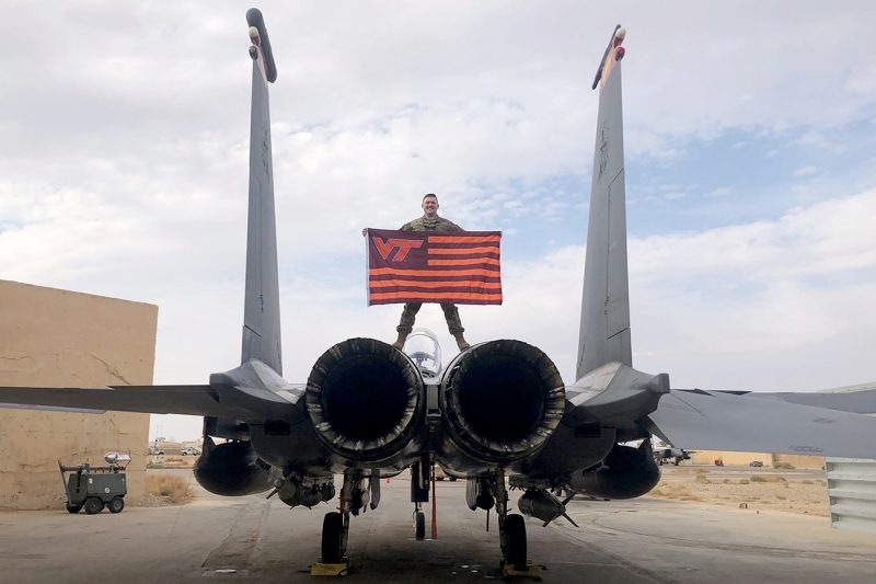 U.S. Air Force 1st Lt. Joshua Preiss holds a Virginia Tech flag while standing atop an aircraft.