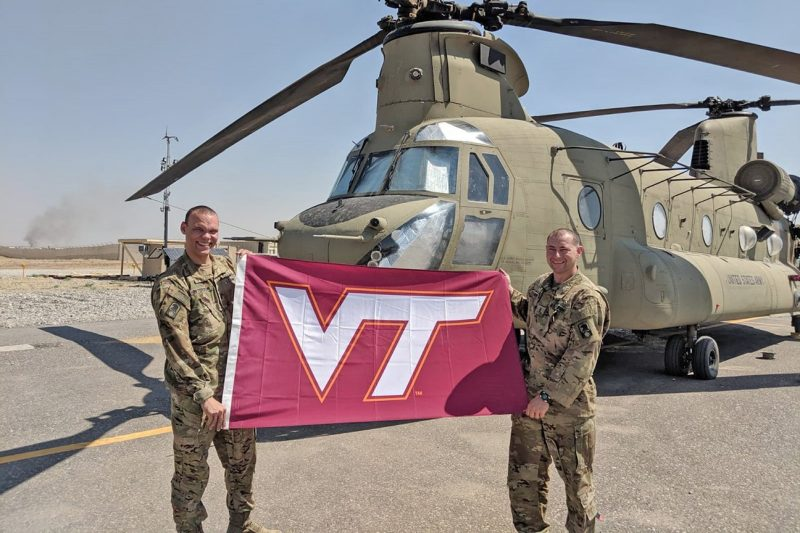 U.S. Army Chief Warrant Officer Chris Toler, at right, holds a Virginia Tech flag with 1st Lt. Marco Peterson.