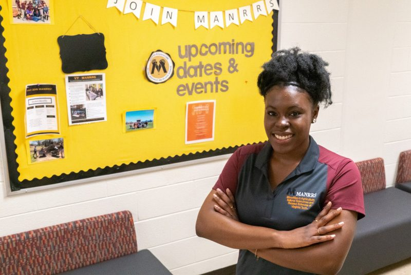 Graduating senior Marquelle Benn stands in front of a MANRRS bulletin board.