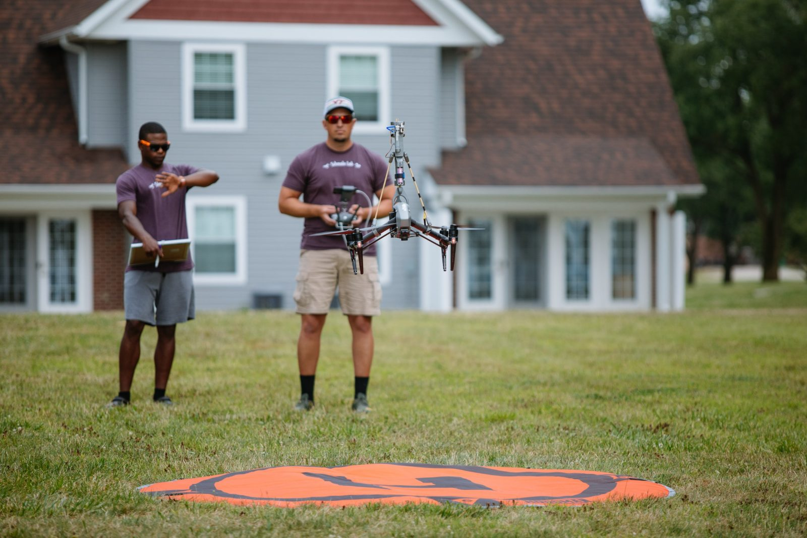 "Undergraduate student Bryan Bloomfield (left) from Morehouse College examines his watch as David Schmale (right) in manning a sensor-mounted drone. An orange circle with an ""H"" is located underneath the hovering drone. Courtesy of Christina+David."