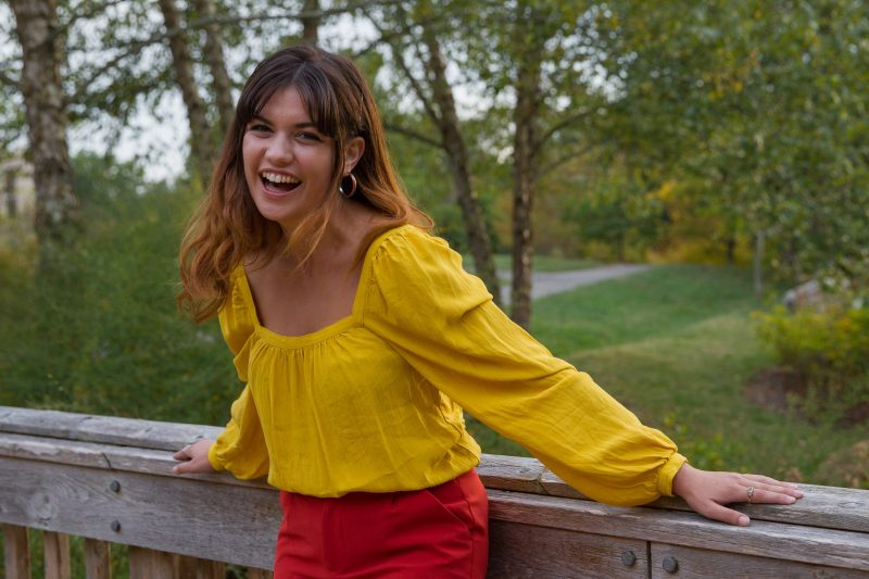 Portrait of a smiling Ellie Muraca wearing a yellow top and red pants