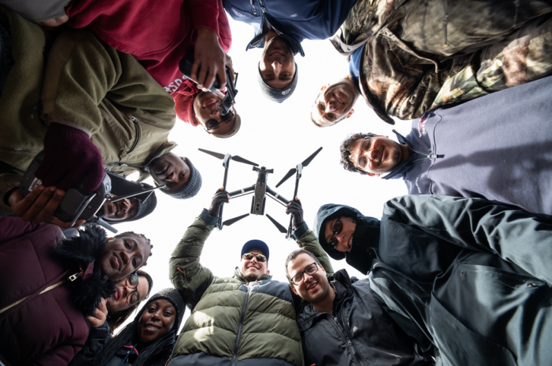 David Schmale (bottom, center) and Shane Ross (top, right) and their students are corralled in a circle and looking down at the camera. Schmale is holding a white unmanned aerial vehicle, also known as a drone. Peter Means for Virginia Tech.