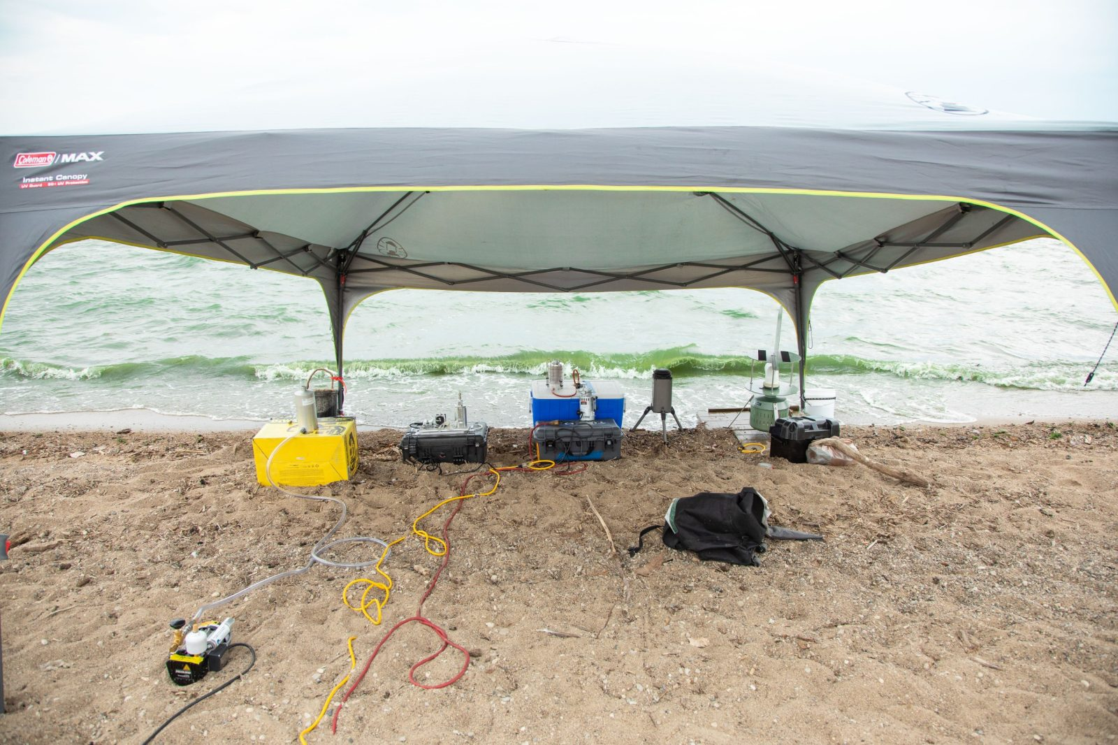 A large grey tent is located on the shoreline of Grand Lake St Marys, Ohio. Under the tent, aerosol-monitoring equipment is collecting data on harmful algal blooms. Courtesy of Christina+David.