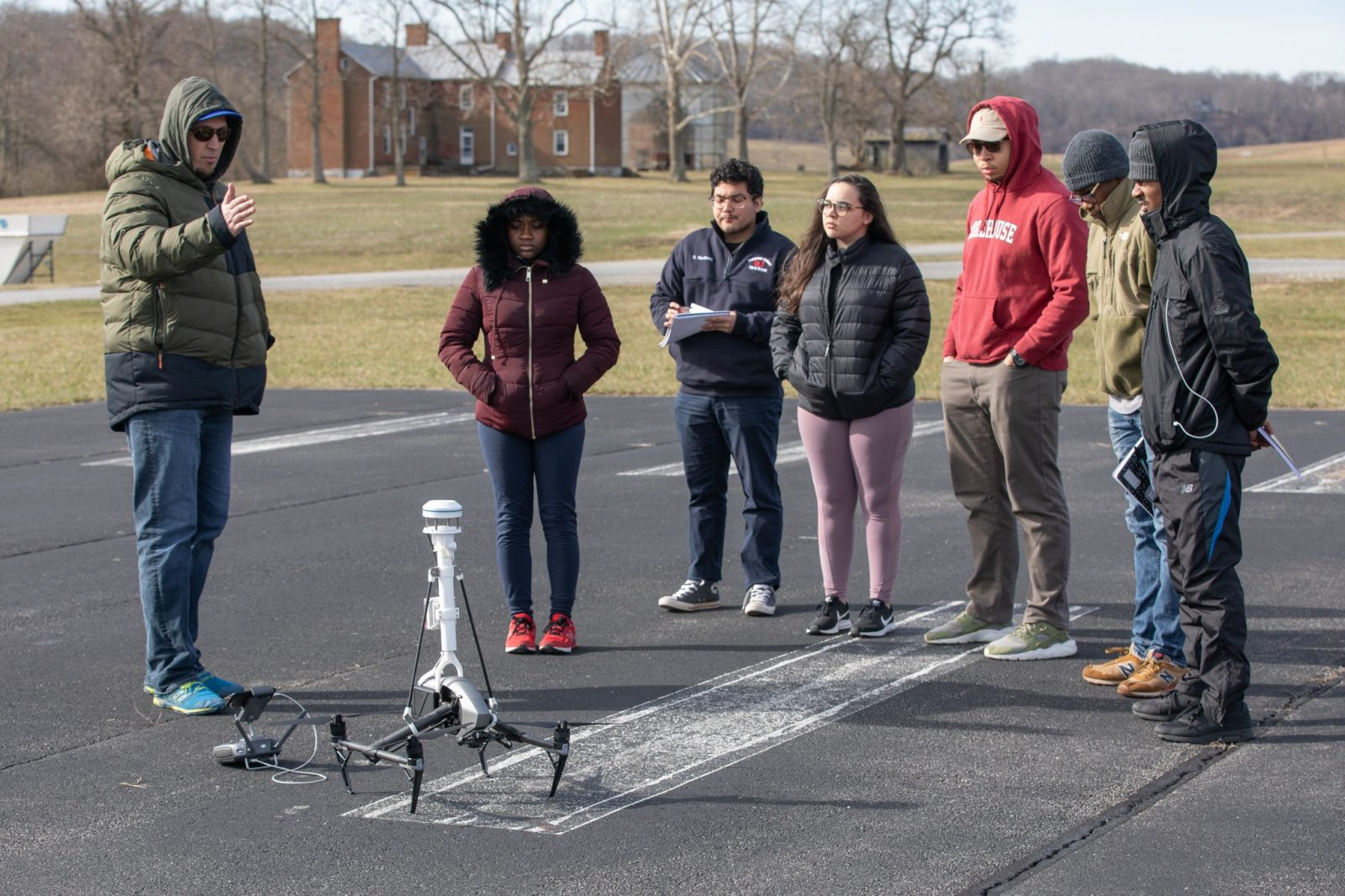 Undergraduates from Bennett, Morehouse, and Hampden Sydney stand on an airstrip at Virginia Tech's Kentland Farm. They look at a drone as David Schmale prepares them for a data sciences mission to monitor wind  Courtesy of Peter Means.