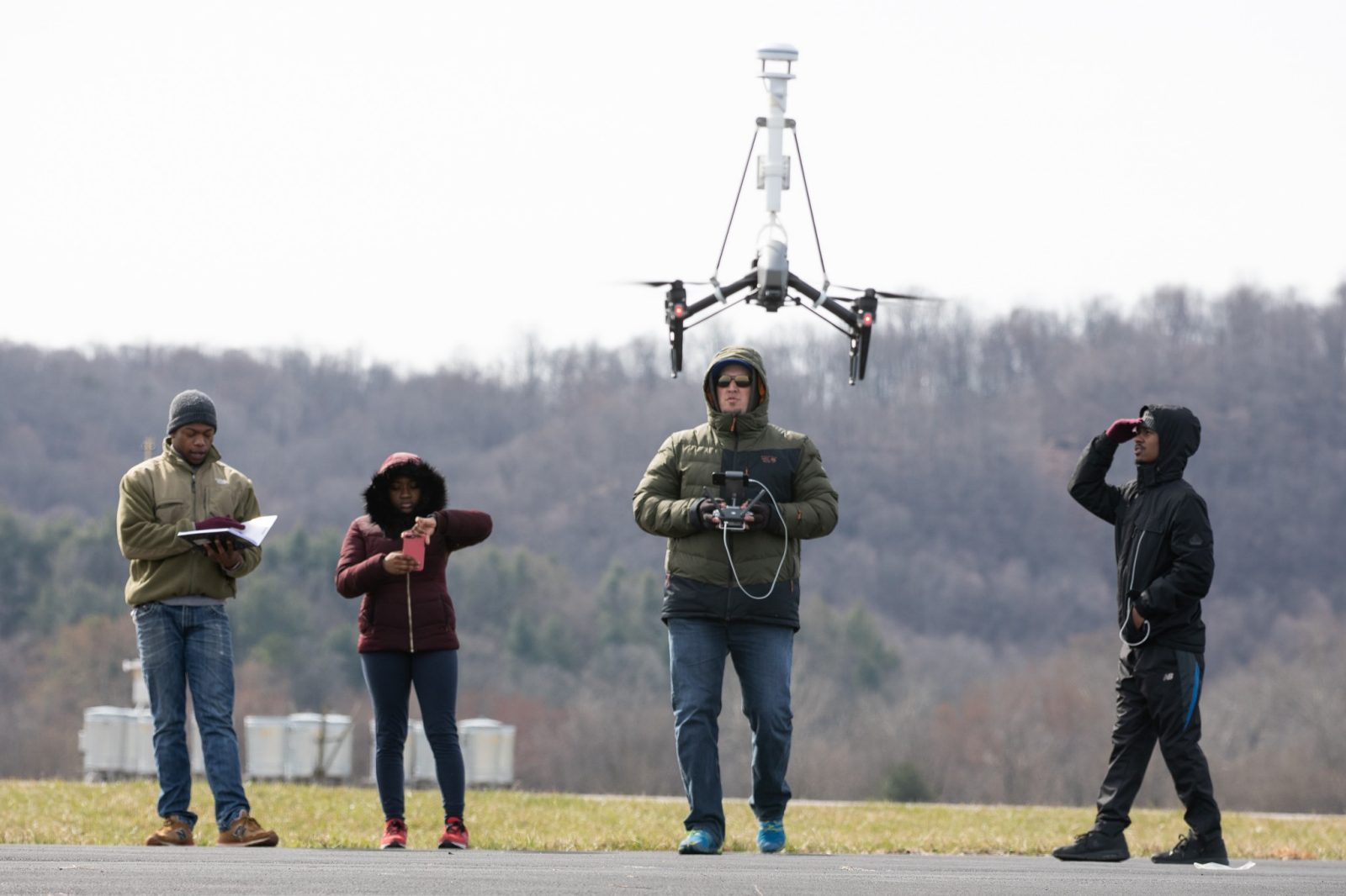 Undergraduates from Bennett, Morehouse, and Hampden Sydney stand on an airstrip at Virginia Tech's Kentland Farm. David Schmale is manning a drone. One student is writing in a notebook, another is recording a video on her phone, and another is observing the drone and protecting his eyes with his hands. Courtesy of Peter Means.