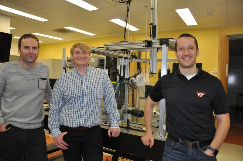 Jason Holliday, Hal Holmes, and Eli Vlaisavljevich (left to right) pictured in front of a customized histotripsy transducer in the Vlaisavljevich Laboratory.