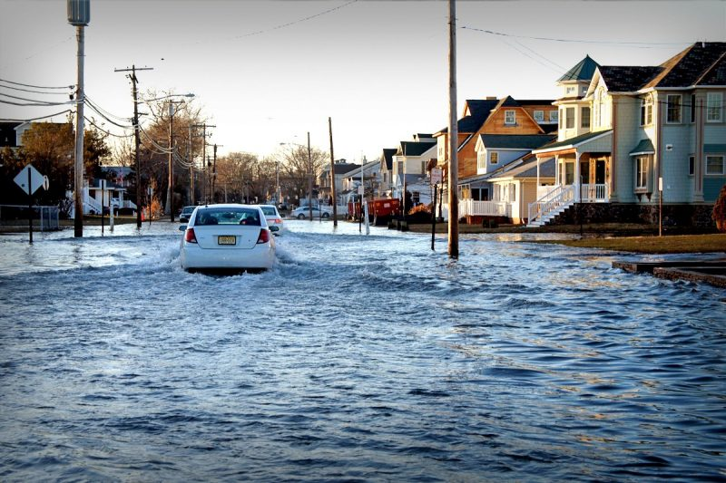 A white compact care traverses a flooded street in Hampton Roads, Virginia. The wake reaches is hitting telephone and electric poles that line the streets. The flooding is so high that the water reaches the porch steps of homes.