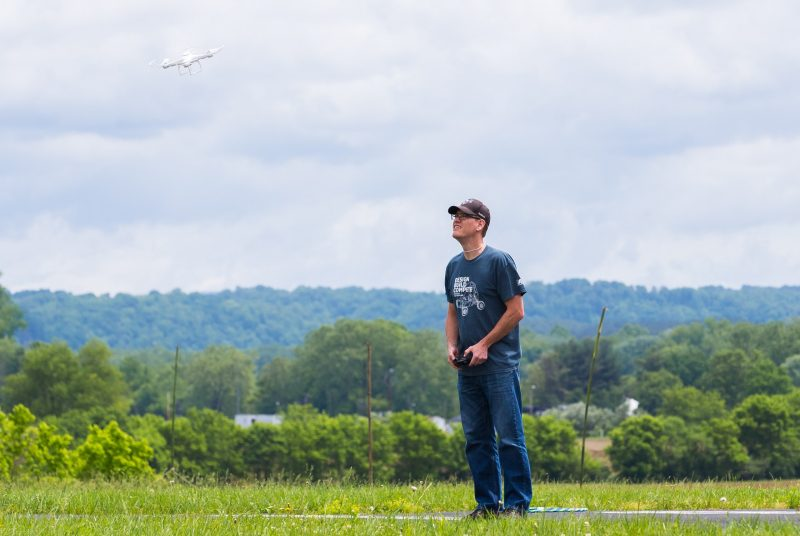 A man stands in a field holding a controller while a small white drone flies nearby