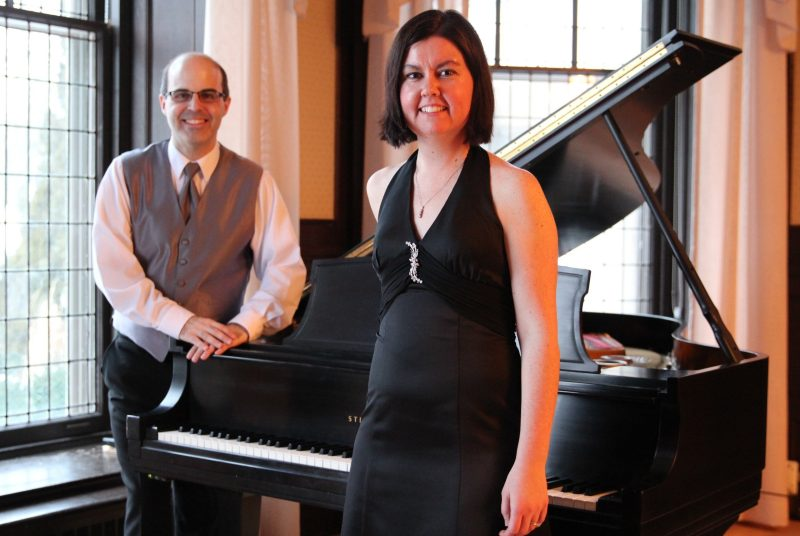 Canadian pianists Gregory Millar and Lisa Raposa, the Millar Duo, stand in front of a grand piano.