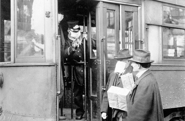 A street car conductor wearing a mask is not allowing passengers aboard without a mask during the 1918 flu pandemic. Courtesy of National Archives. The conductor is leaning out the front door of the trolley to speak to two men.