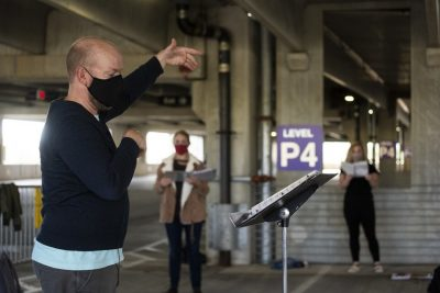 Person leading singing in parking garage