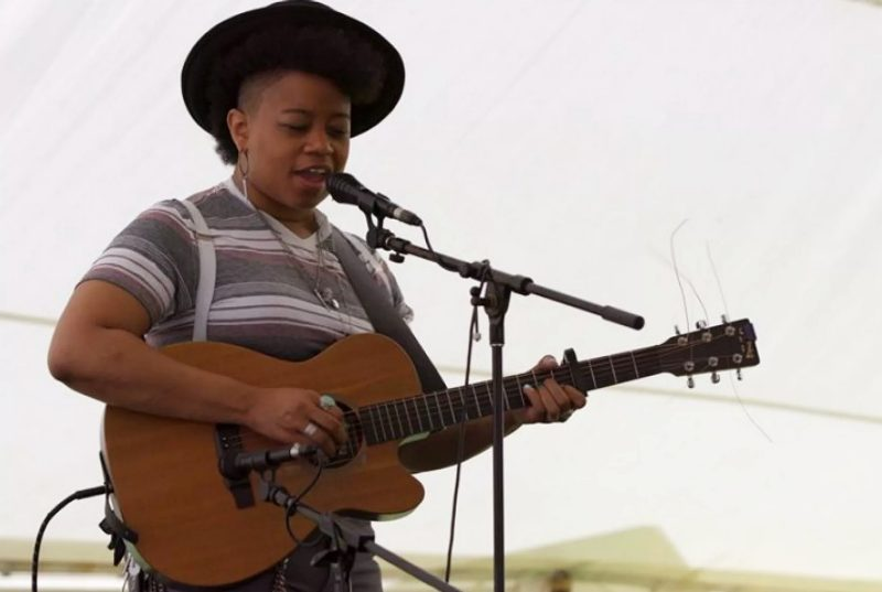 A young black performer plays a guitar and stands at a microphone sining.