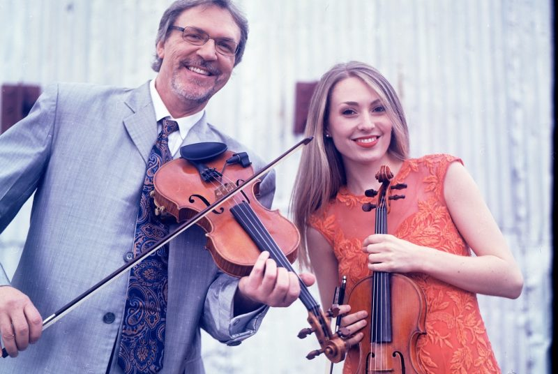 Mark and Maggie O'Connor pose outside in front of a barn holding their fiddles.