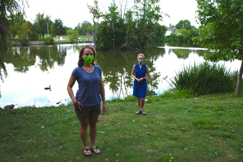 Nicole Ward, a doctoral student, and Cayelan Carey, an associate professor, both in the Department of Biological Sciences pose at the Duck Pond. Each is wearing a mask and standing more than six feet part.