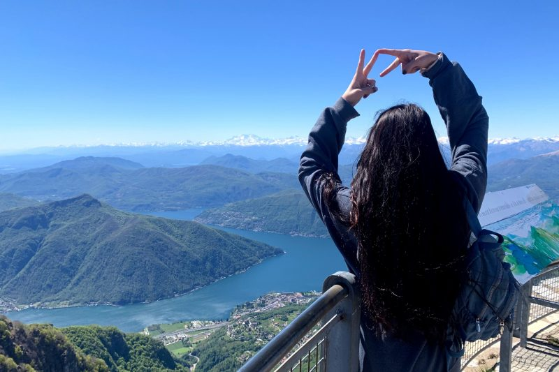 Student holds up a VT sign as she overlooks a lake in Switzerland.
