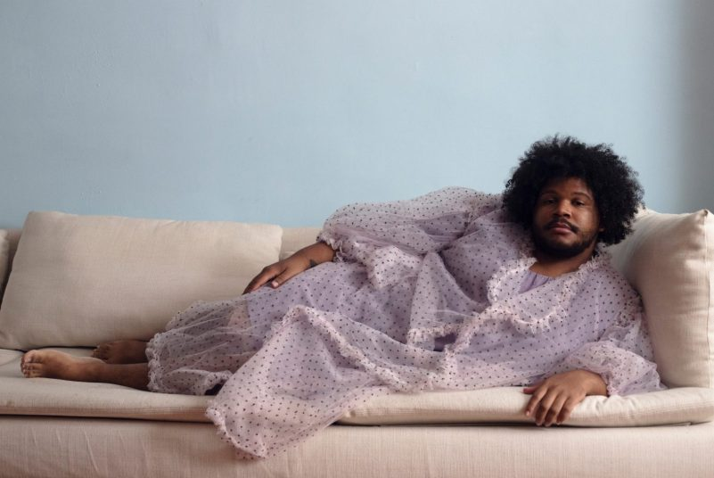 A Black man wearing a sheer pink robe reclines on a beige sofa
