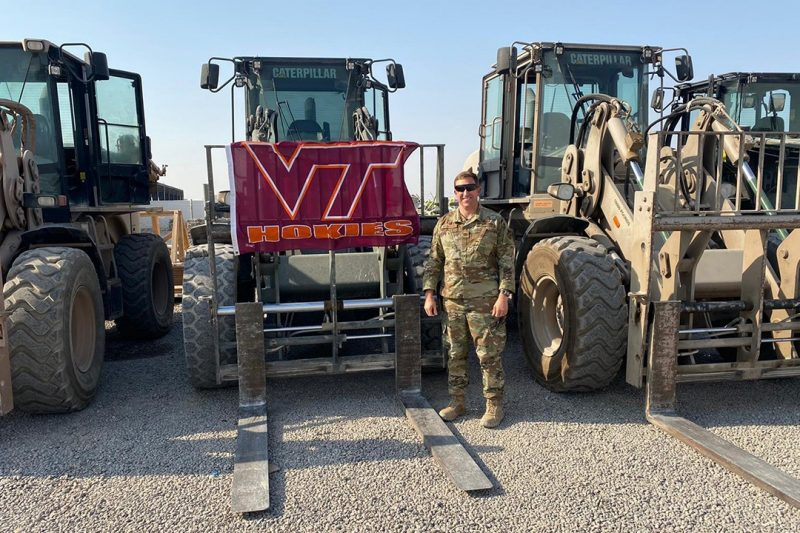 Maj. Michael Biederman stands in front of a row of heavy equipment and next to a Virginia Tech flag.