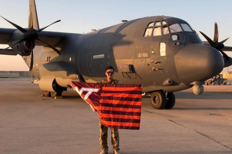 U.S. Air Force Capt. Jordan Schafer holds a Virginia Tech flag in front of an HC-130J, a fixed-wing search-and-rescue aircraft.