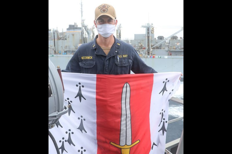 U.S. Navy Ensign Jake McCormick holds a Corps of Cadets flag while standing onboard the USS Cole.