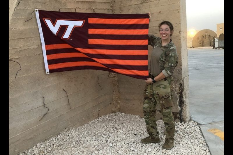 Capt. Kimberly Markovcy Veal holds a Hokie flag against a concrete wall while deployed to southeast Asia.