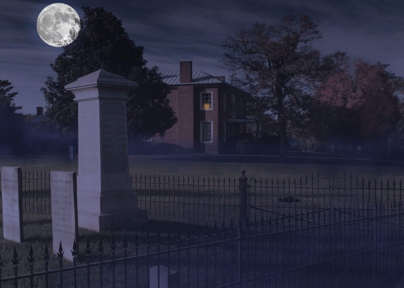A photo illustration shows the Reynolds family graveyard at night in the foreground as a full moon rises over the darkened house