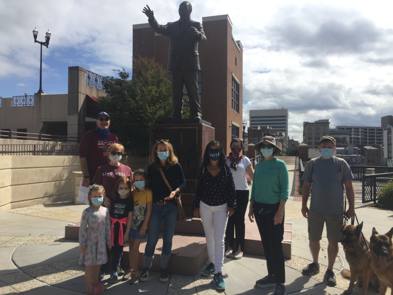 Seven adults, three children, and two dogs stand in front of the Martin Luther King, Jr. statue.
