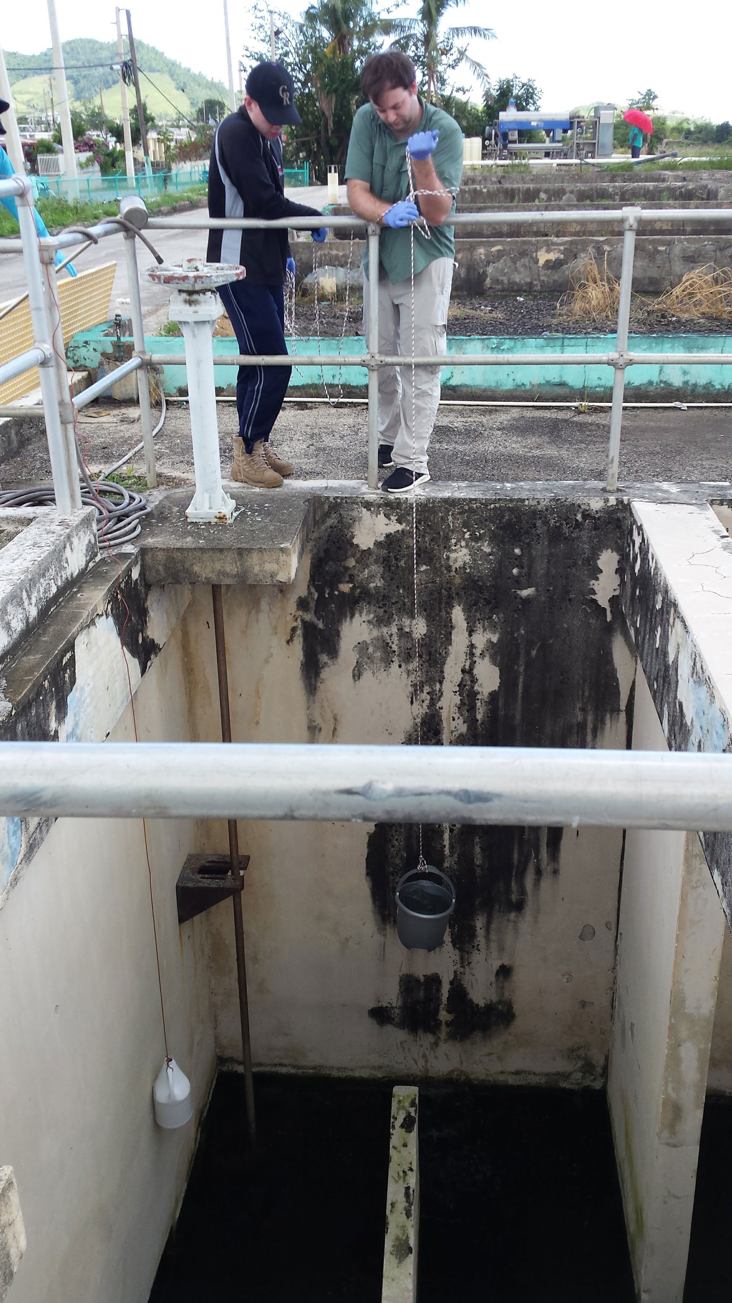 Doctoral students, Benjamin Davis, also first author of the published research, and Matthew Blair, sampling a Puerto Rican wastewater treatment plant.