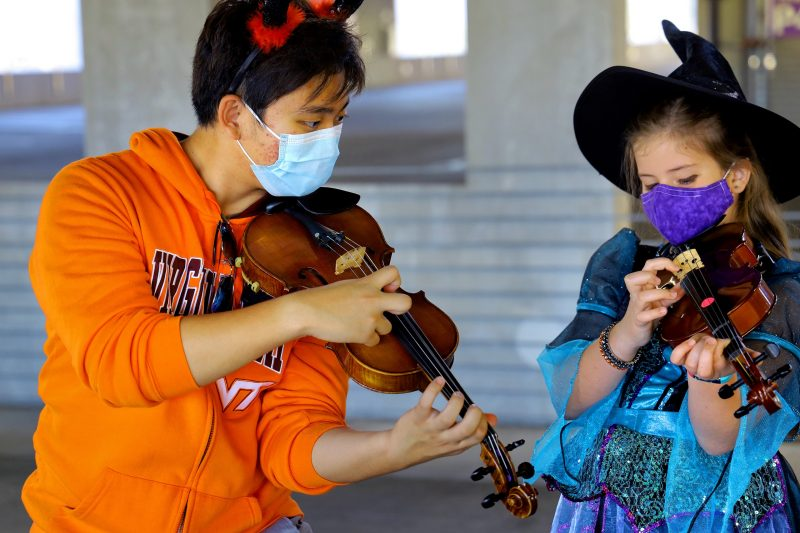 James Kim, a first-year music education student, instructs a Montgomery County student. They both donned Halloween costumes for a special Virginia Tech String Project gathering in the Perry Street Parking Garage.