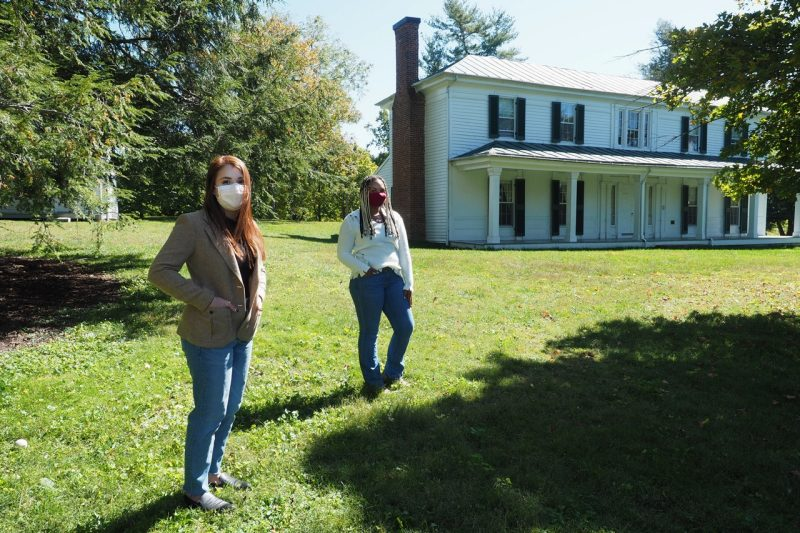 Isabella Jimenez and Kaylee Crockett stand in front of a historic house