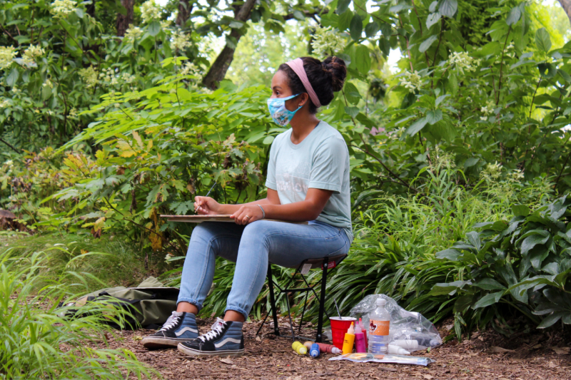 A student paints at the Hahn Horticulture Garden
