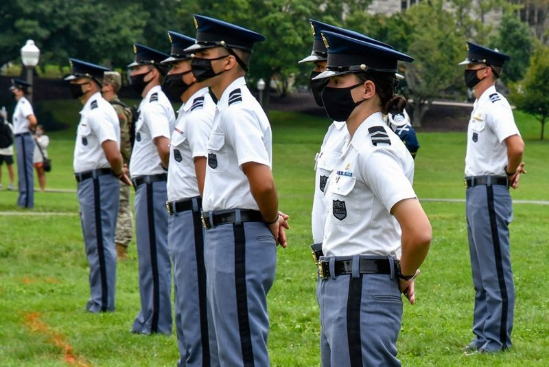 Cadet Erin Cross-Kaplan, at right, stands at parade rest in a line of cadets on the Drillfield during a military parade.
