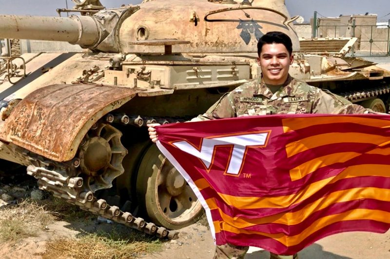 U.S. Army 1st Lt. Peter Unpingco holds a Virginia Tech flag in front of a tank while deployed to Afghanistan.