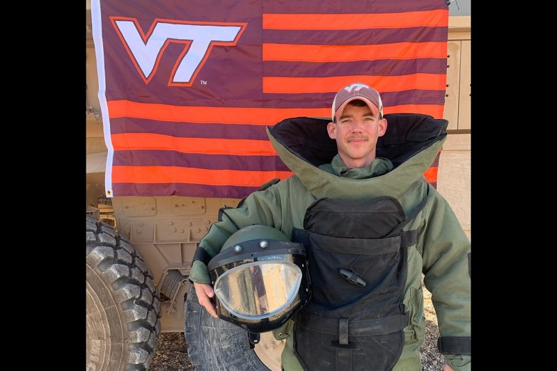 U.S. Army Sgt. Alexander Unkle, explosive ordnance disposal technician, stands in protective gear in front of a Virginia Tech flag.