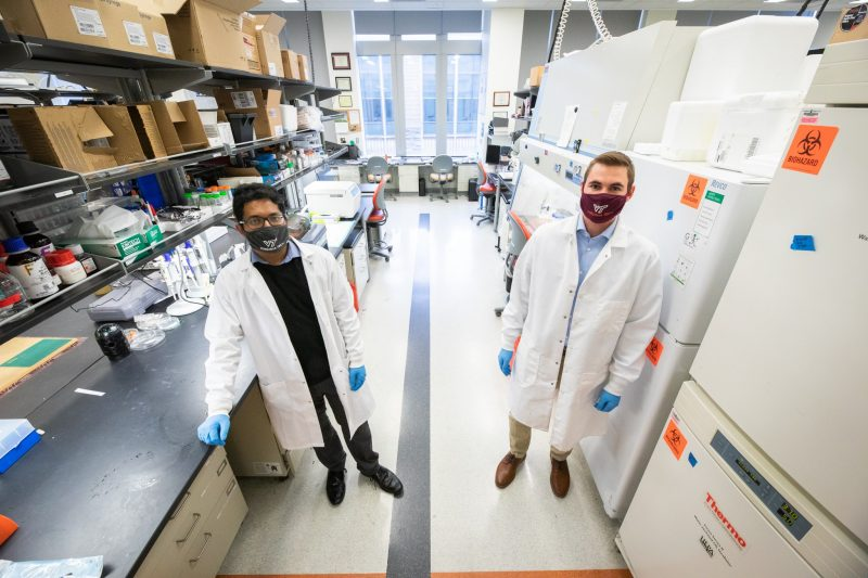 Doctoral students Graybill and Jana stand in a research lab, with masks and lab coats on.