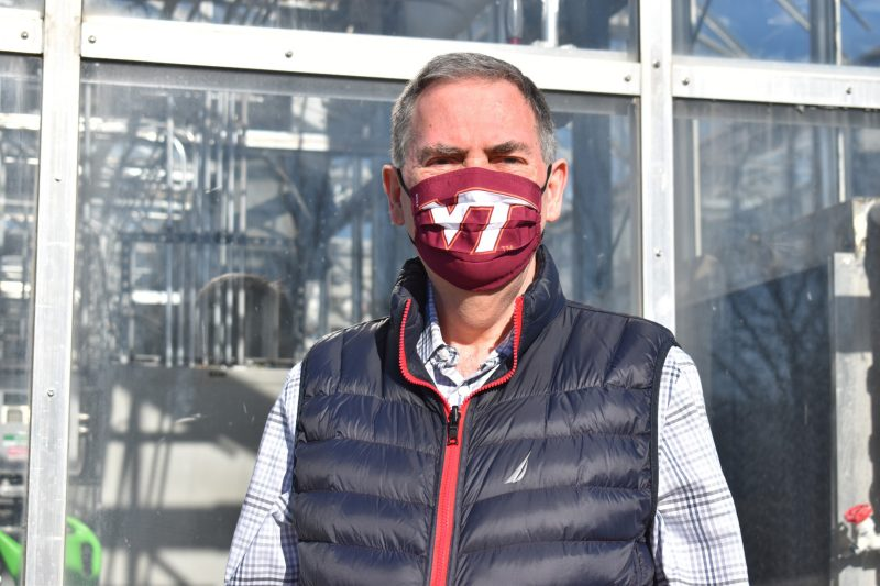 Erik Nilsen poses at the Virginia Tech Plant Growth Facility built on Smithfield Road. He founded the facility in 2007. Nilsen is wearing a Virginia Tech branded face mask and a plaid shirt. Photo by Steven Mackay.