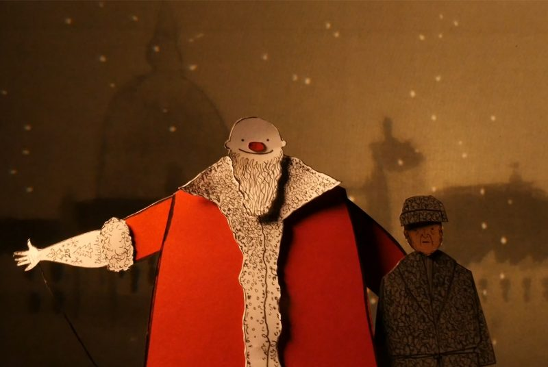 "A puppet version of Santa with his arm outstretched stands beside a puppet version of Scrooge in this scene from Manual Cinema's ""Christmas Carol."""