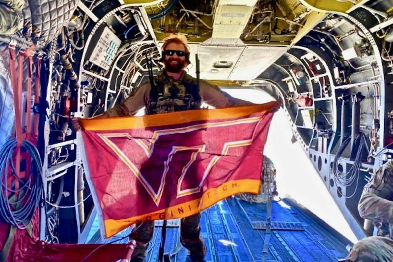 U.S. Air Force Capt. Garrett Treaster holds a Virginia Tech flag while standing in an aircraft.