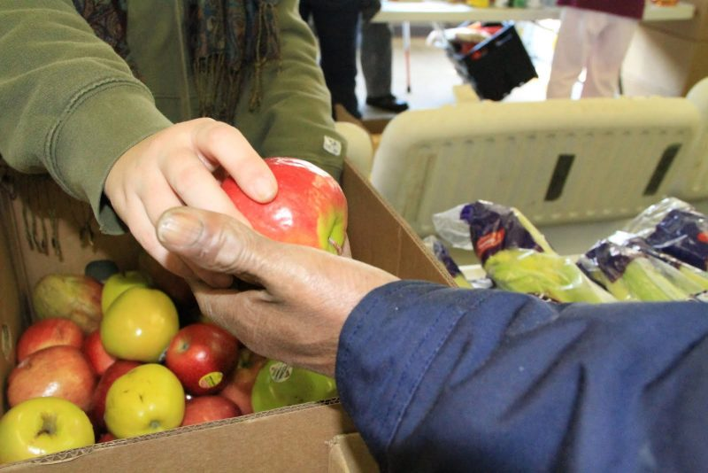 photo of a person handing someone an apple